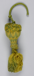 Tassel made up of parts of an earlier tassel. Head is vase-shaped and covered with green and yellow silk in a chevron pattern. Collar of green and yellow looped silk. The head is inverted and has hanging yellow and green threads bound at the top to form a tassel. Green silk cord knotted into the top.
