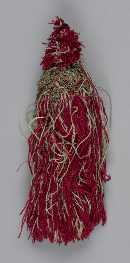Skirt of red and white threads partly covered with a trellis of silver threads over a soft core. Topped with an ornament of red and white threads.