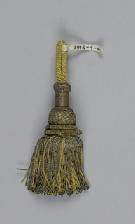 Tassel with a turned wooden core (cylinder, bulb and flange) covered with yellow silk and gilt threads in wrapping, trellis, and twisted rolls. Skirt of twisted yellow silk and gold threads. Loop of yellow silk cord at top.