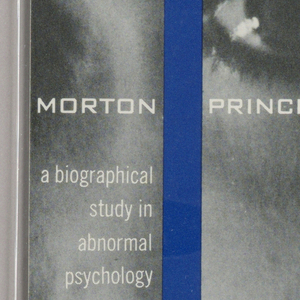 "Cover design for ""The Dissociation of Personality,"" by Morton Prince. Multiple black and white photographs of a woman's face in vertical bands conjoined by vertical blue bars. Photos do not directly align to create clear image. Printed text in white."