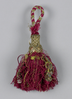 Skirt of red silk threads with four ornamental strings. Head is turned in a vase shapes, painted gold and partly covered by gilt braid in woven design. Loop of woven braid in silk and metal threads.