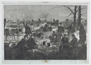 Horizontal view of a group men seated and standing about an open fire in the foreground with a large number of covered wagons in the background.