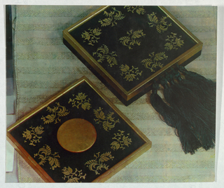 Two square-shaped boxes, designed as product packaging, are framed in actual or simulated wooden or metallic material. Eight foliate forms in brown on a black background are arranged around the four sides of the box covers. One cover design features an additional foliate in the center and five knotted black tassels attached to the rim; the other has a centered circle of the same material as the rim. The boxes are displayed on a striped chevron-patterned fabric background.
