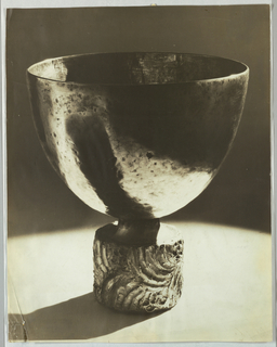 The drinking component of the object has the appearance of hammered metal, while the base shows raised elements, perhaps encrusted with gems. Dark shadows and bright highlights alternate in the depiction of of both object and background in the photograph.