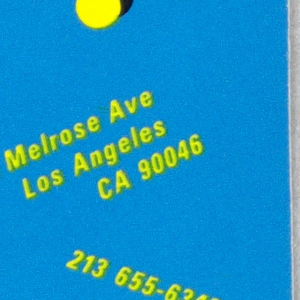 Business card with text in yellow on blue background. In black box, angled: Vertigo; floating red and yellow dots with black shading. On the right, angled text: 7550 Melrose Ave / Los Angeles / CA 90046 / 213 655-6343.
