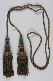 Pair of tassels separated by twisted cord. Green and rust.
