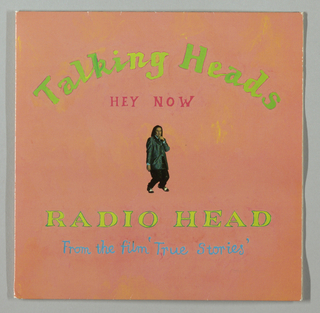 Recto: On a salmon colored background, in the top half, Talking Heads is imprinted on a curve in green in upper and lower case partly connected letters; immediately below, centered, Hey Now is imprinted in bright pink. In the center, there is a photograph about two inches high of a long-haired singer in a zoot-styled shiny jacketed suit; his lege are bent, his left arm holds a microphone to his mouth and his right arm hangs straight down. Blue collar and cuffs peek out from the jacket and black and white shoes are seen beneath the cuffs of the black pants. Beneath the figure, Radio Head in chartreuse capitals outlined in green appears on one line and From the film 'True Stories' appears in upper and lower case blue script. Verso: On a chartreuse background, an illustration of a multicolored painted accordian appears in the center. In small black capitals, Radio Head is imprinted above to the left and below to the left and right, while Hey Now is imprinted above to the right. Production information appears below each of these four song title listings and A and B, in capitals, are imrpinted to the left and right respectively of the central illustration. Inside, left: There is a photograph of a group of boys, roughly arranged in a row, wearing green shirts and dark pants (jeans?). The shirts have identical unidentified insignias on the top right. The boys are waiving sticks in their upraised arms, are open-mouthed and appear to be calling out. Toward the center, one boy is holding an unidentified animal (dog? pony?) on a leash; to his right, another boy holds an unidentified object in one hand. From left to right, just behind the boys, are utility poles; on the right is a swing set and on the extreme right a partial view of a house. A pale blue cloudy sky appears in the background and dried brown earth and grass occupy the foreground. Inside, right: A night color photograph of the inside of a bar or clubhouse, in predominantly pink and purple tones, shows a man and wom