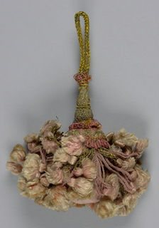 Skirt of pink silk threads supporting pink tassels partly covered with gold threads. These support pink silk tassels covered at the top with pink silk fringe and pink and gold threads in chevron pattern. Head, a small vase shape above the ball, is covered with gold thread. Cord is braided yellow silk and gold threads.