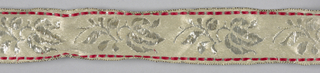Trimming or ribbon with a flower and leaf motif in silver, repeated at intervals on ground of white silk with red silk borders.