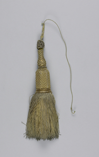 Tassel with a skirt of metallic threads with collar at top. Head of wood painted gold (vase above hexagon) and covered with metallic threads in knotted design; knob at top and loop of cord bound with metallic threads.