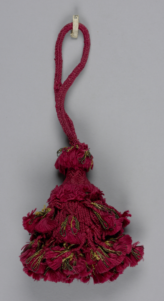 Skirt of red silk threads, knotted and twisted and ornamented with two rows of tassels of red silk and gilt thread. Head covered with red silk in chevron pattern. Loop of red silk cord.