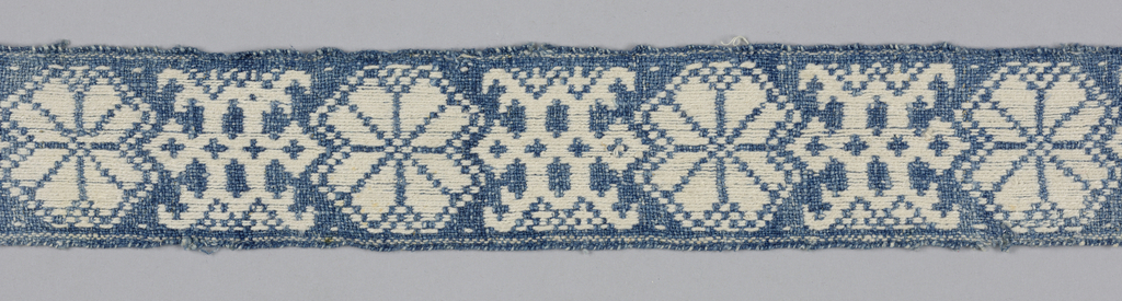 Narrow band patterned by an alternating geometric blossom and geometric leafy branch or vine in blue and ivory.