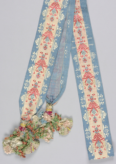 Sash of sky-blue ribbon patterned with a broad central band with a symmetrical repeat of stylized heart and arabesque forms in blue, coral, and cream warp floats. Hanging decorations are formed from knots and flowers of silk floss and basket-like forms of bobbin lace and leno weave of silk and linen cord.