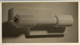 The present black and white photograph displays an unidentified object, perhaps a radiator or plumbing fixture, fabricated of a ceramic material. A roller (?) is inserted in two ribbed ceramic end pieces. A protruding attachment with a metal base and ceramic handle is inserted in the end piece located on the right. A partly flat-surfaced and partly ribbed ceramic structure, perhaps attached to a frame, appears behind. Light is reflected in the ceramic ribs; deep shadows form in the background.