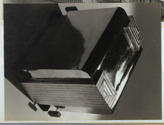 The present photograph features a rectangular object, fabricated of metal, with rounded corners on the upper edges. The shiny, unadorned surface is interrupted on the two narrow ends by a stepped design, which begins on the top and segues into a center section of vertical ribbing, visible on the side panel in the photograph (and, it is assumed, duplicated on the other, non-visible side.) A narrow metal stem with a rectangular terminal, perhaps fabricated of black Bakelite, protrudes on the right end. The object is possibly a heater, intended to rest on the floor; or a tabletop object, such as an unfinished prototype of a toaster or radio cabinet.