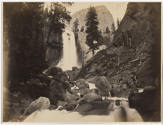 View of mountain in the distance, waterfall at center, trees, rocks and water in foreground.
