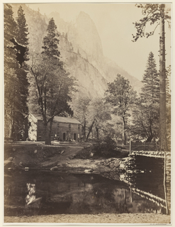 Within forested landscape, two-story house with people in front. Shore in foreground; large mountain in background.