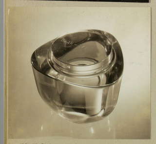 A three-sided jar with rounded corners is fabricated of a transparent material, either glass or plastic. The photographer has placed the jar in the center and used bright lighting to create surface highlights.