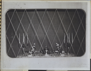 A cloth-covered dining table is viewed within a box-like structure fronted by diamond-shaped metallic grill work. Place settings (china, silver and crystal) are visible on the side closest to the viewer. Four-stemmed candelabra are placed at either end. An unidentified object, flanked by flower arrangements, comprises the centerpiece.