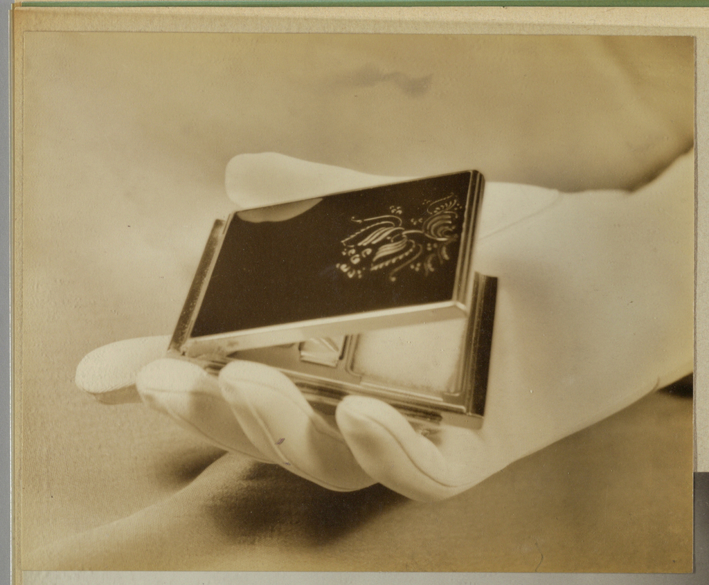 Photographed on a woven fabric background, arranged so as to form curves, a woman's hand, clothed in an opaque white fabric glove, extends diagonally across the page from the upper right to the lower left. Three fingers cradle the bottom half of an open compact, while the thumb just touches the far side of the lid. The compact is framed in metal, and a foliate motif, which appears to have been fabricated of metal, perhaps silver, adorns the lower half of the black lid, perhaps onyx. The powder compartment inside the lower part of the bottom half is glimpsed beneath the open lid.  Deep shadows in the fabric appear under the fingers and alongside the edges of the glove above the wrist, where the glove abuts the edge of the page.