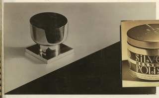 In the present black and white photograph, the page is divided by a diagonal line stretching from the lower left hand corner toward the upper right hand corner, ending about an inch below that corner. The featured object, a metal doorknob, is placed on the left in the upper half, which is shaded in tones of gray; the object casts a shadow on the left. Light is reflected in the shiny surface of the doorknob, a streamlined circular object set in a square base. The lower half of the page is black.