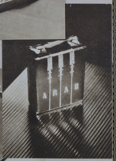 A box, which appears to be fabricated of paper and is shaped like a cigarette package, is placed on the diagonal on a ribbed fabric background. The front, which faces the viewer, features a design of three vertical lines placed at equal intervals between the top and bottom edges. Jewel-like terminals positioned at the tops of  the verticals extend about one quarter of the way downward. The block capitals of the product name, Arab, are interspersed between the verticals. The front surface of the box is brightly lighted, while highlights alternate with dark shadows on the box top and the ribbed surface.
