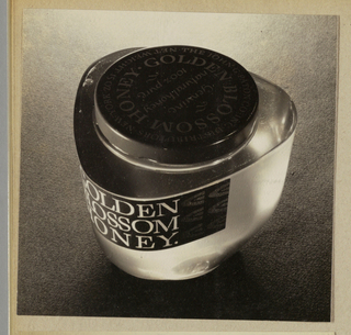 The present black and white photograph displays a three-sided jar with rounded corners fabricated of a transparent material, either glass or plastic. Pasted just under the edge of the rim, the jar's black label is imprinted Golden/ Blossom/ Honey in white serif-style type. The round screw-on jar lid, centered within the rim, is imprinted in the same type, in a circular format, Golden Blossom Honey; additional type encircles the product name, and Genuine/ natural honey/ 100& pure is imprinted in hand-lettered style type in the center. The jar is posed in the center of the photograph on a textured carpet. Light bounces off the surface, particularly under the label and on the right side of the rim.
