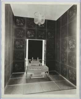 The present view of a room installation featured in a Metropolitan Museum exhibition shows a central and two lateral tiled walls on a tiled floor. The tiles, in a foliate pattern, are arranged in five horizontal rows on the walls and three on the floor. A niche is centered on two vertical rows of tile in the back wall and placed between the floor and the top of the third level of tiles. A full length mirror within; glass shelf across; and stoppered, glass perfume bottles and tasseled boxes placed on the shelf comprise the vanity. A curved, tufted bench, also tasseled, sits on the floor in front of the vanity. Hanging above the vanity, a chandelier of curved, blown glass strips and narrow, fluorescent bulbs located in a central core, completes the design.