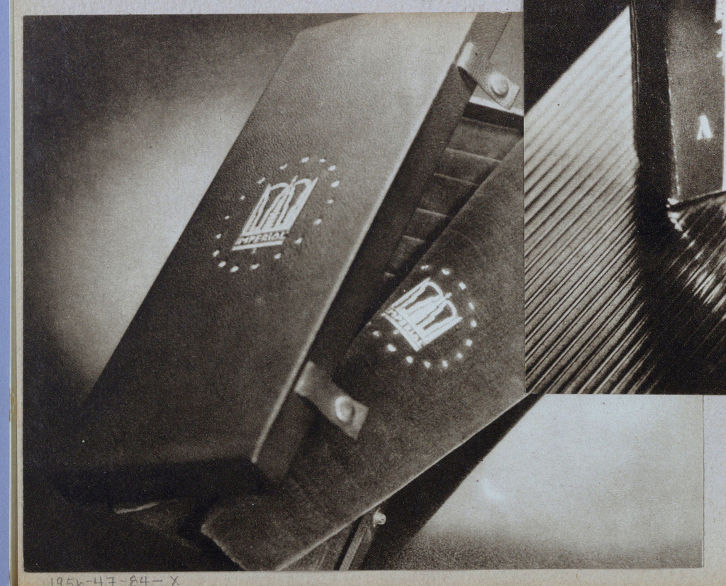A partly opened box, which appears to be fabricated of leather (exterior) and velvet (interior) is placed on the diagonal and abuts the top and bottom edges. A design, perhaps of crowns or castle spires, imprinted below Imperial in capitals, is centered on both the cover and the exposed lining; a circle of indecipherable letters rings the central image. Short straps in which snap tops are embedded extend from the cover; with the box in a closed position, these would attach to snap bottoms, one of which is visible on the lower part of the box.