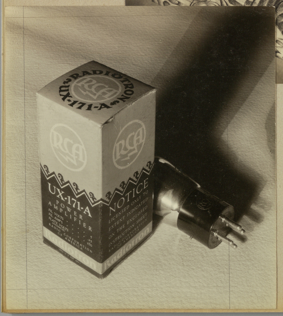 On a pebbly-textured background in the present black and white photograph, a tall, narrow rectangular box is displayed on the left. Two sides of the packaging, gray in the upper half and black in the lower, as well as the top, also gray, are visible. The logo, in white, centered in the upper half of each side and on the box top, is comprised of a circular rim enclosing the letters RCA in the designer's serif style type, with the left stroke of the A extending downward in a thunderbolt symbol. At the intersection of the black and gray areas is a frieze comprised of discretely rendered abstract foliate icons in black above a thin band of rickrack in white. Copy relating to the product fills the remaining space in the lower halves, and a continuing gray band just above the bottom is imprinted Radiotron. A circle of bold type in black surrounds the logo on the box top. The contents, a plug, are placed diagonally to the right and in front of the box. Dramatic lighting highlights the glass surface of the plug and casts deep shadows next to the box and plug on the right.