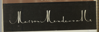 "The company name, Maison Mendessalle, is imprinted on coated black paper in white in a hand-lettered style upright script, in which the height of the capital ""M"" and letter ""l"" are exaggerated."