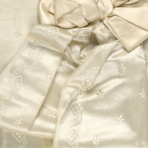White satin bow with two long pieces of broad figured white satin ribbon with fringed ends. Possibly part of a dress trimming.