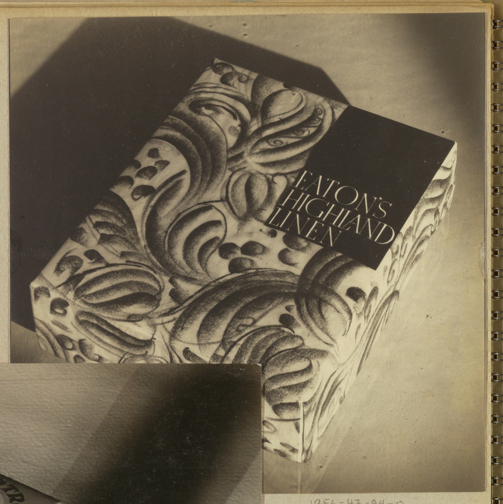 In the present black and white photograph, a box designed to contain stationery is positioned on the diagonal and occupies most of the page. Swirly foliate forms comprise the all-over pattern on the top and sides of the box. In the upper right hand corner, a black rectangle is imprinted in its lower half, left margin justified, in white serif style capitals, Eaton's/ Highland/ Linen. The box casts a dark shadow on the left and is reflected in the lower front and right side of the background, probably a glass or plastic surface.