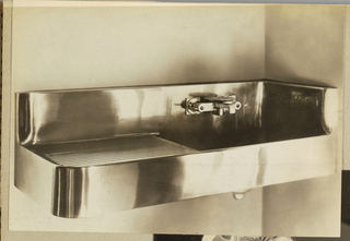 The present photograph features a single drainboard sink fabricated of Monel (tm) metal with a faucet-cum-soap-dish mounted on the backsplash behind the basin. The photographic lighting design achieves a pattern of light and shadow playing on the metallic surfaces.