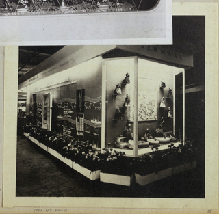 In the present photograph, three dimensional models and graphics comprise a display of Danish agricultural products in a pavilion. In a three-sided, glass fronted, electrically lighted case on the right, dolls in Danish costumes, probably representing such products and their geographical origins within Denmark, are mounted on the back wall, flanking an agricultural map of Denmark. Abutting the case on the left, a panel, not enclosed by glass, depicts agricultural exports through illustration and type. At the top, a cornice is labeled Denmark Agricultural Products on the long side; Denmark is repeated on the short side. Flower boxes are placed in a row on the floor immediately in front of the pavilion.