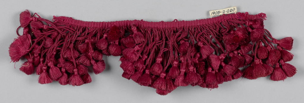 Red fringe with a heading and skirt threads of a graduated length forming a scalloped edge. Each thread is looped and twisted and supports a tuft of red floss.