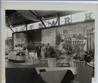 In this partial view of a Danish Dairy Products Display, the backdrop, center right, features a white-coated technician seated in front of machinery designed to produce butter. The apparatus consists of a series of interconnected pipes and gears connected to a central mechanical churn, operated by the technician. To the right of the technician, Danish/ Butter, in white serif-style block capitals, superimposed on the image, is followed by twelve lines of copy about the product. In the center of the photograph, three unidentified men, dressed in suits and ties, are posed against the backdrop. A gate, fronting the trio of men and the butter display, is patterned in interconnecting triangular-shaped outline, perhaps fabricated of metallic wire. Three Danish-designed upholstered armchairs, their backs to the viewer, are spaced at intervals behind the gate. On the left, three smiling women, visible above the waist and dressed in white puff-sleeved garments, are posed behind Danish food products in a glass display case, flanked by flowers. The image terminates below in a curved, ribbed-wood structure on a black base. Denmark, in large block serif-style capitals, fabricated in three dimensions, stretches across the pavilion frame on top.