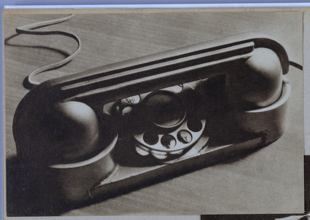 The present photograph features a telephone in the streamline style. The narrow rectangular base supports a rotary dial in the center, and on each side, a raised, rounded terminal designed to cradle the receiver. Parallel to the base is a ribbed bar attached on both ends to the tops of the spherical objects which serve as the mouth and ear pieces. One rib, longer than the others, curves over the smaller end piece where a short piece of the attached cord is visible. Highlights and shadows in the photograph emphasize the sleek and compact design of the instrument.
