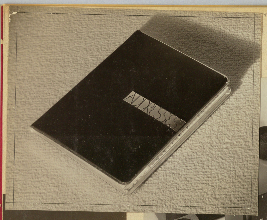 In the present object, an address book is photographed on the diagonal against a textured background, either fabric or carpet. The cover appears to be fabricated of gilt-edged black leather with rounded corners and is punctuated by a contrasting horizontal band positioned at center level and stretching from left-of-center to the right edge. Addresses, in a hand-lettered type, is imprinted in capitals on the band. An alphabetical index appears behind the cover at the right edge.