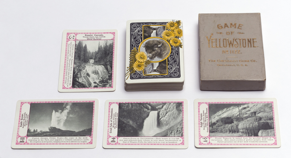 Deck of 52 playing cards with half-tone photoillustrations of the scenic wonders of Yellowstone National Park. Uniform decoration on backs of buffalo and wild flowers. Gray cardboard box with gilded lettering and one card listing other games by the same company. Cards are oriented both horizontally and vertically with printed text describing each scene.