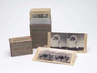 Red paper laminate (cardboard) box with removable top, with printed black text on brown paper front, back and top. Contents: 36 stereoviews (albumen silver prints) of the major scenic views of Yellowstone Park mounted on cream cardboard.