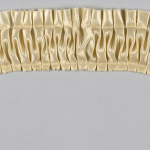 Collar made by pleating an ivory-colored ribbon with a small woven ornament.