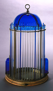 Table type circular dome shape cage of glass, with frame of Sheffield plate. Concealed door. Wood base has two brass pins (b,c) for supporting floor (d). (e) and (f) are blue glass food containers and (g) is tassel of red silk and gold braid.