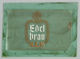 Small ovoid shapes fill a square frame with rounded corners. The bottom of the frame splits, left and right, and Ale, in serif-style capitals, is imprinted within the space where the frame would have been. A decorative ornament, foliate or pseudo-heraldic, extends upward from the center of the frame at the top. Inside the frame, Edel/ brau is imprinted in Old English letters. A decorative narrow, broken line extends across the top and bottom of the sheet. The design color scheme is gilt for all components excepting Edelbrau, which is white.