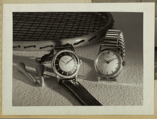 In the present black and white photograph, two Universal Geneve watches are positioned in the center and center right, with a tennis racket in partial view behind and two golf tees to the left. Variations in light and shadow bouncing off the textured background and the wood frame of the racket focus interest on the watch faces and bands, one metal and the other leather,