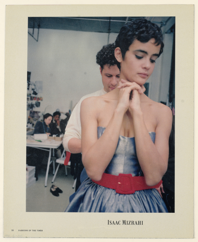 The photograph, situated in a fashion office/ workroom, features a head-to-hip view, occupying the full vertical space to the right of center, of a model with black hair in a gamine style, wearing a strapless dress that shows some cleavage, in a shimmering blue-gray fabric, with a full, gathered skirt, and a wide red belt at the waist. Her arms are bent and her fingers are clasped under her chin; her head is turned slightly to her left and her eyes are cast downward, emphasizing her heavy black eyelashes and eyebrows. The designer, Isaac Mizrahi, whose bent head and downcast eyes focus on adjusting the back of the dress, stands behind the model; the top of his head is at the level of her ear, the left side of his face is partly obscured by her upper body, and the right shoulder and arm are partly visible. A pair of shoes, perhaps Mr. Mizrahi's, is on the floor immediately to the left, while  further back, two seated figures at a table and an assortment of photographs, papers and boxes are visible. The whole is set within a white border. On bottom, right of center, the designer's logo is imprinted and in the bottom left-hand corner, Fashions of the Times appears.