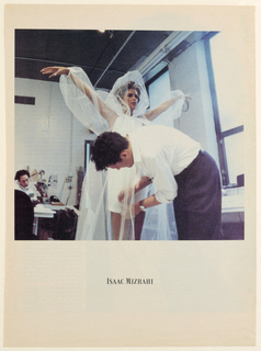 The photograph, situated in a fashion design office/ workroom, features a three-quarter length view of a model wearing a white, above-the-thigh, sleeveless bridal dress with a halter-style shirred neckline. The dress is overlaid by a white, transparent, hooded, tulle coat, apparently full-length, with long, full sleeves, gathered at the wrist. The model is turned slightly to her left and her arms are upraised in a V-shape. Isaac Mizrahi, the designer, wearing dark trousers and a white dress shirt with the sleeves rolled up, is leaning across the model, with his head bent and eyes focussed on the hem of the dress, which he is pinning. Light from the window on the right is centered on Mr. Mizrahi's shirt, while artificial light illuminates the rest of the scene. On the left, behind the model and designer, is a fashion assistant, seated at her desk, with a white telephone cradled in her right ear. There is a variety of papers and photographs on the worktable and wall behind the assistant. The photograph is set on a white page and the designer's logo is imprinted beneath.