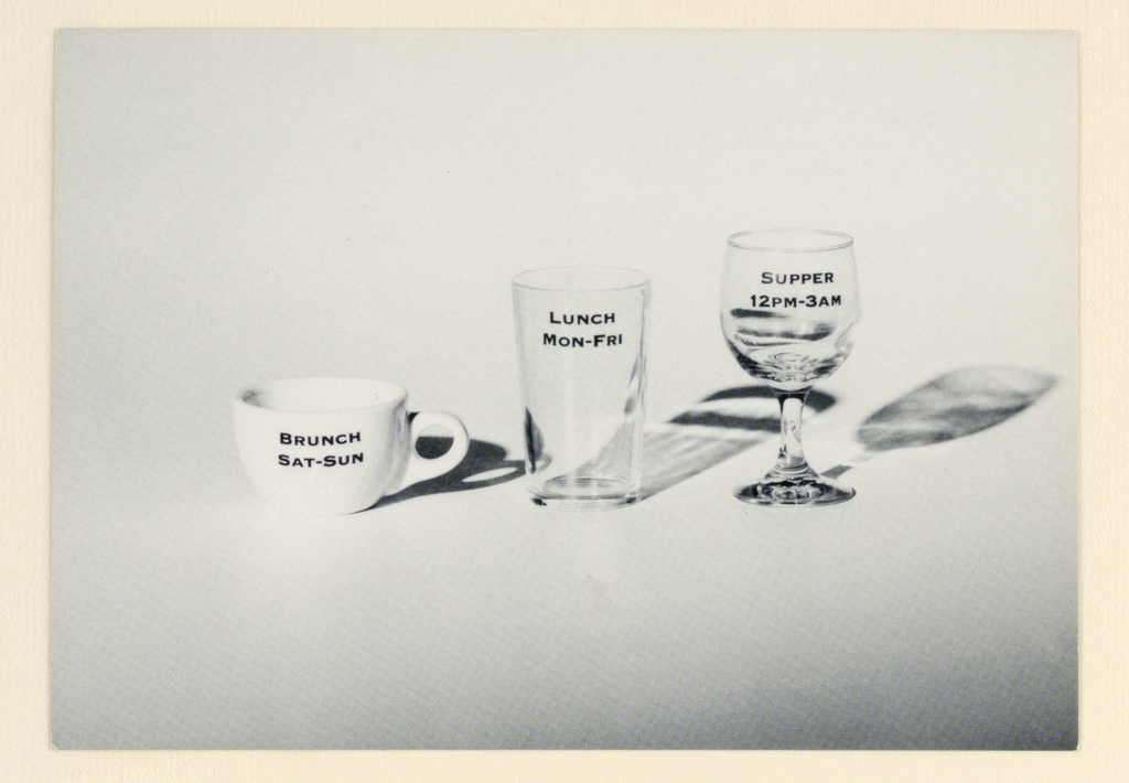 Recto: On a pale gray-toned background, across the center from left to right, is a photograph of a white china coffee cup, and a water glass and wineglass, both transparent. All three cast shadows to the right and are imprinted in small black capital letters with the types of meals offered at particular times: the cup, Brunch/ Sat-Sun; the water glass, Lunch/ Mon-Fri; the wineglass, Supper/ 12 PM-3 AM.   Verso: The restaurant's name, address and telephone number are imprinted in small capitals on four lines, the name in bolder and darker type, at the top left. A narrow vertical line separates the message area from the addressee area; Place/ Stamp/ Here is imprinted in the latter, top right.