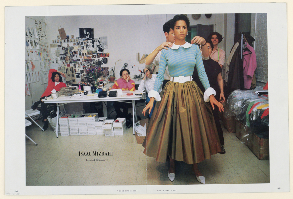 In the printed photograph, the model, posed right of center in a full frontal view, and probably facing a mirror, is wearing a dress composed of a horizontally striped, long-sleeved, predominantly blue-green top, trimmed in white collar and cuffs; and a cocoa brown, full, gathered taffeta skirt, with a wide white belt, within taffeta loops, at the waist. Pointed, buckled white shoes and daisy-shaped earrings complete the ensemble. Isaac Mizrahi, the designer, standing behind her slightly to the left, with his head and face only partly visible and his gaze focused on her right shoulder, his arms bent, his hands at her shoulders, and a necklace matching the earrings in his left hand, is perhaps about to place the necklace around the model's neck. Back and to the right, two figures of assistants, one in a pinkish shirt with a green tape measure around his neck, the other in black, look straight ahead, probably into the mirror. To their right, a standing coat-tree holds several coats, and in front of that, there are belts in several colors laid out on top of plastic sheeting, covering large cartons resting on the floor. On the left rear side, there is a table filled with transparent boxes of buttons and other trimmings, as well as desktop office items (pencils, tape, etc.). Beneath the table, several tiers of shoe boxes, labeled Manolo Blanik [shoe designer], are stacked seven across, with the shoes on the top tier exposed. Three people with weary expressions are seated in casual poses at the table. Fashion photographs and sketches are tacked in several rows, almost to the ceiling, on the wall behind. The Isaac Mizrahi logo, superimposed on the floor tiles, appears in the lower left, with Bergdorf Goodman [department store], in smaller type, just beneath. In the surrounding white border, at the bottom, Vogue March 1991 is imprinted.