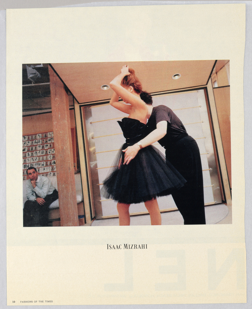 A color photograph shows a profile view of a fashion model in a black, strapless dress with a short, full tulle skirt. Her arms, elbows bent, are raised in front to touch her upswept hair, so as to partly block her face; her left ear is visible, as are part of her nose. mouth and chin. Isaac Mizrahi, the designer, in black t-shirt and pants, is standing behind her, leaning forward and placing his arms around her skirt, so as to adjust it, apparently while looking in a mirror opposite, but hidden from the viewer. There is a partial view of his head and neck, but his face is obscured by the model's upper body. The backgound of the room (or partition) is pitched at a steep angle, so as to make the figures appear to lean further forward than they actually do. On the left, a man, seated, in a dress shirt and trousers, his left arm bent and his chin resting on his hand, his right arm in his lap, is looking at the designer and model. On the wall behind him, a display of fashion images is hung. The Isaac Mizrahi logo, in black Boldoni, fairly small, is centered beneath the photograph. The whole occupies most of a white background page, the designer's logo appears in the center in the white space below the photograph, and Fashions of the Times is imprinted in the lower left-hand corner.